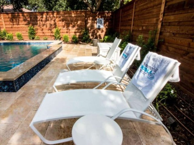 A pool deck with three poolside chairs and a small table