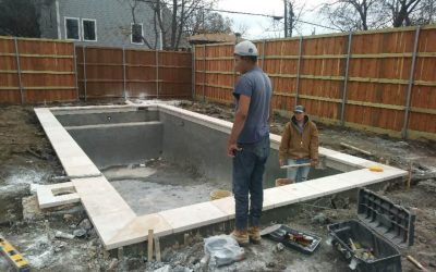 Two pool technicians working on a pool