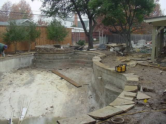 A pool in the middle of a remodel surrounded by construction materials