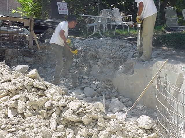 Workers demolishing the steps of a pool