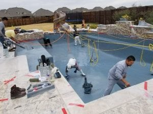 Workers actively resurfacing a pool