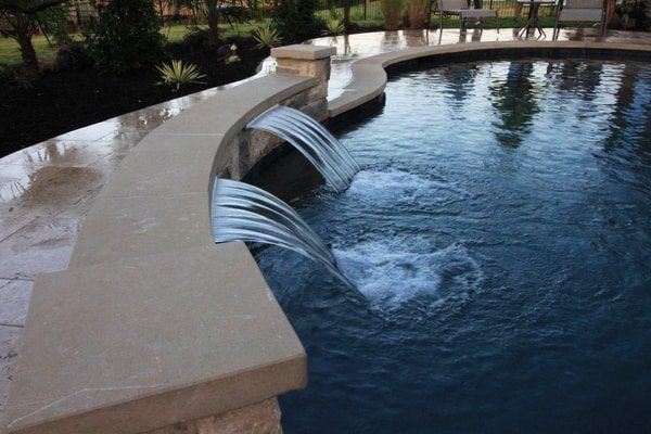 New water feature installed in a pool surrounded by a deck and landscaping