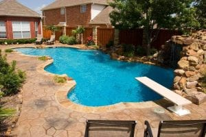 freeform pool with diving board and waterfall