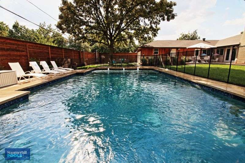 Beautiful rectangular concrete pool with pool chairs on the side