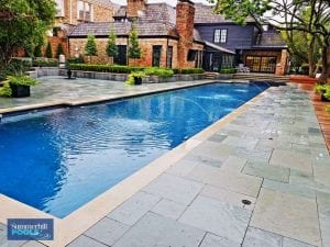 modern pool with new stone decking