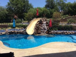 Rock waterfall with slide going into the pool