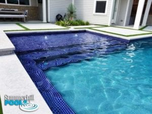 backyard pool with blue glass tanning deck and bubblers