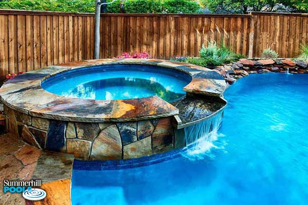 stone spa with water wall into a pool